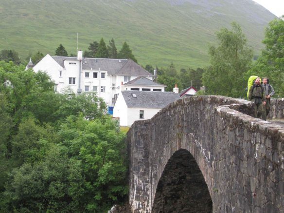 The anceient Bridge of Orchy (with two walkers on it) and behind it the Bridge of Orchy Hotel, a busy oasis for West Highland Way walkers.