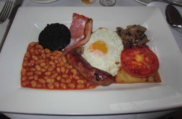 The dreaded full English breakfast. Top left: black pudding. Bottom right (under the tomato): fried spud